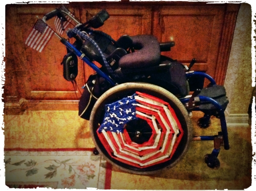 side shot of Mac's manual chair showing two small USA flags on each handle and the wheels with stylised/woven plastic to emulate the US Flag, woven red and white stripes on 3/4 of the spokes and blue woven with tiny white knots on 1/4