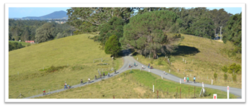 shot of all 20 kids in the distance on a country road 17 on bikes and three running behind. Mac in his trailer on the back of the bike. more like bike specs in the distance than clear images.