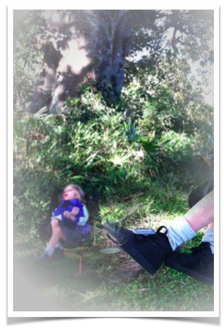 A shot of Mac sitting in the distance in front of our giant Moreton Bay Fig tree in our garden, dappled light coming through, school uniform, black converse high tops.  Blended into the corner of the pic is a close up of his shoes and the small sunsprite device attached to his shoelaces on his left foot.