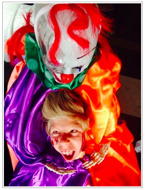looking down from above the skeleton clown head with red flashes of hair, shiny purple and orange satin shirt and one very happy boy with just his head exposed as though the clown is holding his severed head - halloween creeps.