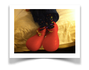 Mac's red plastic oversized clown shoes with spotted socks laying on the crumpled bed after his big night.